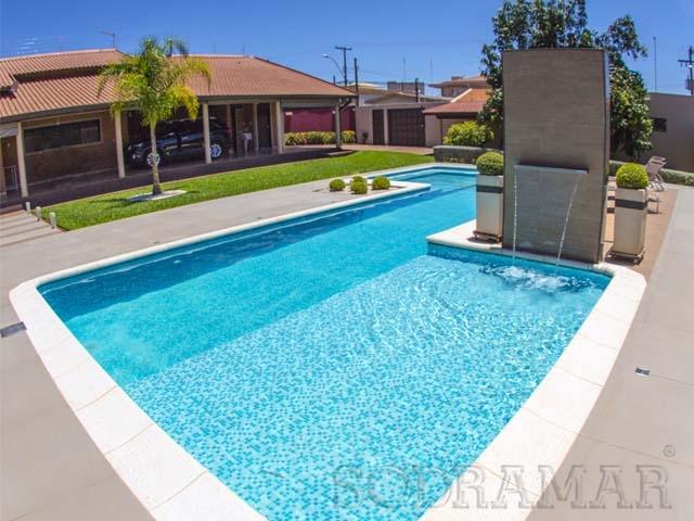 Imagem de uma piscina azul com a água bem limpa e com uma cascata em funcionamento.