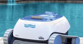 Na beira de uma piscina com cascata está um robô aspirador de piscinas branco e azul.