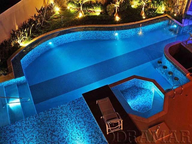 Foto noturna de piscina iluminada