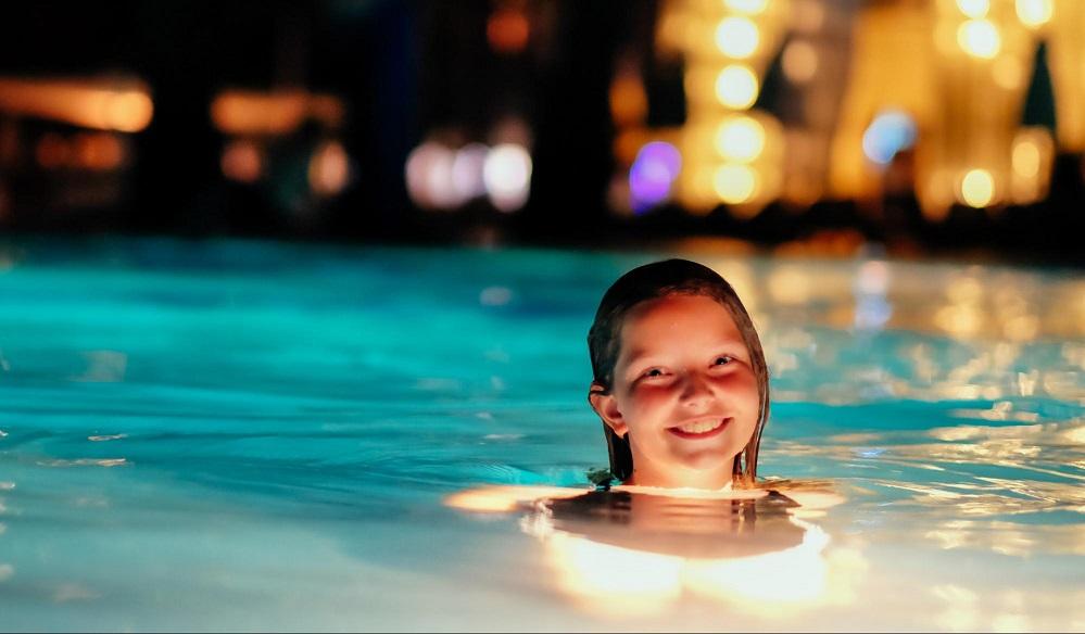 Criança nadando em uma piscina a noite