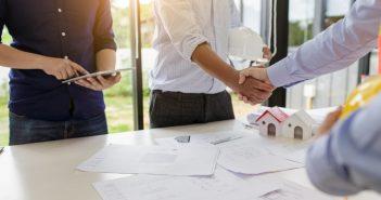 Dois homens se comprimentam em um escritório. Há uma mesa entre eles com alguns projetos arquitetônicos.