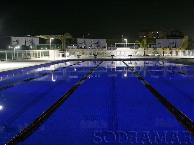 Imagem de uma piscina de clube iluminada à noite