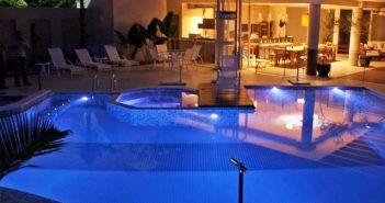 Imagem de uma mão mexendo em um controle remoto apontando para uma piscina